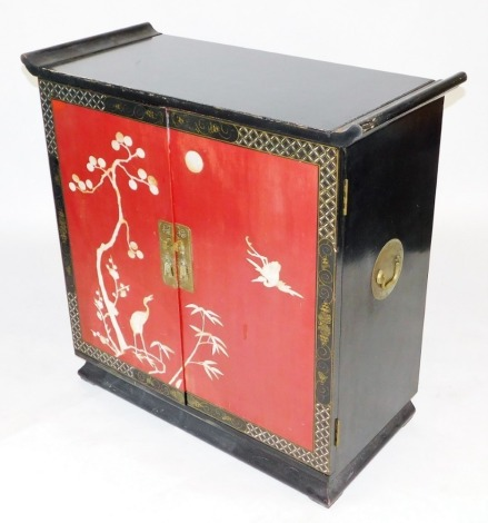 A Chinese black and red lacquered side cabinet, with two red doors inlaid with mother of pearl crane and plant decoration, gilding details and brass handle plates, the interior fitted for bottles and glasses, 98cm high, 101cm wide, 46cm deep.