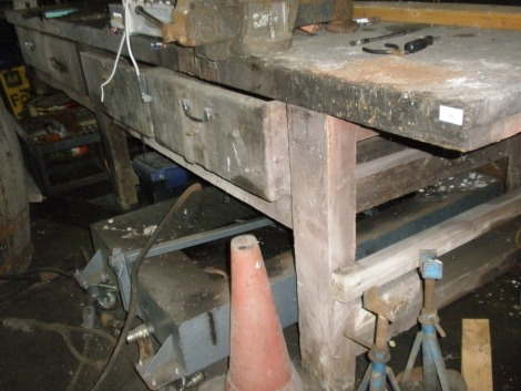 A large wooden work bench for four drawers.