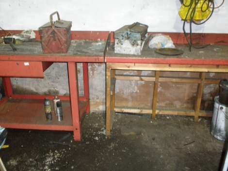Four red steel work benches, one with a wooden base.