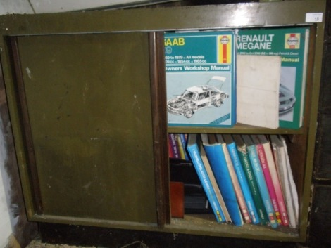 A large collection of Haynes manuals, in a wooden cabinet, plus a further selection currently housed in lot 18.