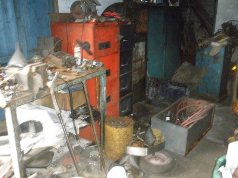 The residual contents of workshop. To include three steel work benches, two filing cabinets, vintage welder, quantity of alloy wheels, vintage tyre remover, pipe bender, carriage jack, bottle jacks, coopered barrel, AA directional marker signs, heavy dut