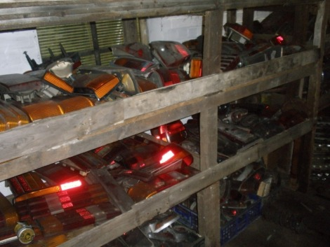 Classic car parts and automobilia, comprising rear light units and wheel trims, mostly from cars of the 1980s/90s, plus two lorry diffs. Situated in main store rear passage on two whole shelf units on RHS (5 bays)