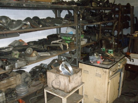 Classic car parts, comprising door mirrors mostly from cars of the 1970s and 80s, headlamp units, water pumps, rack of half shafts, petrol tanks, vintage cupboard and table. All situated in main store rear passage on tall shelves on Ihs, plus cupboard and