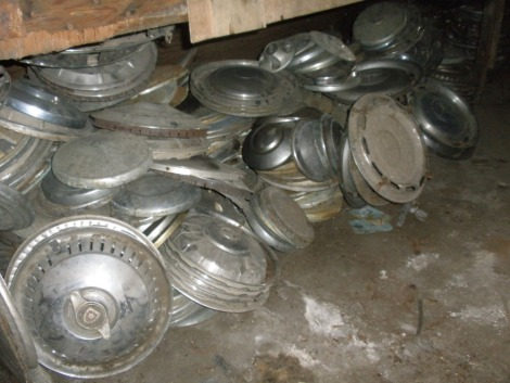 A large quantity of metal hub caps and wheel trims for classic cars, to includ Mercedes, Trimuph, Wolseley, Rover, Daimler, etc. All situated in main store far wall under bench.