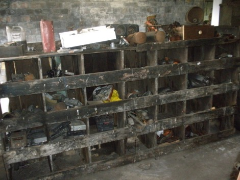 Miscellaneous collectors car parts and automobilia, comprising dials, gauges, wiper motor , radios, car badges, etc. All situated in main store, 5th row, in large wooden pigeon hole shelving.