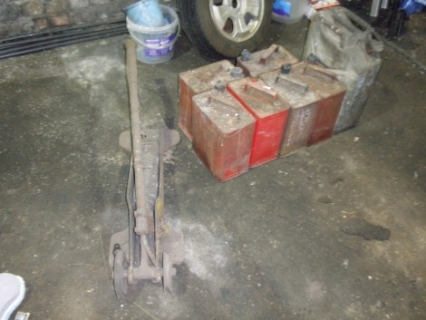 Seven metal petrol cans and a large vintage Dunlop tyre pump. The following lots are situated in main workshop.