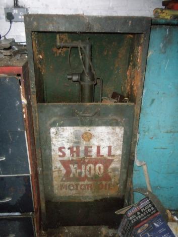 A vintage Shell X-100 motor oil dispenser cabinet.