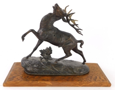 A bronzed spelter figure of a stag, indistinctly signed, 27cm wide, on associated oak plinth.