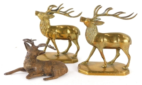 A pair of brass models of stags, each on a canted rectangular base, and a cold painted spelter figure of a recumbent stag. (3)