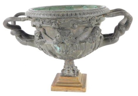 A 19thC bronze two handled urn, cast with bearded gentleman in masks, stylised branch handles on associate column and base, 35cm wide.