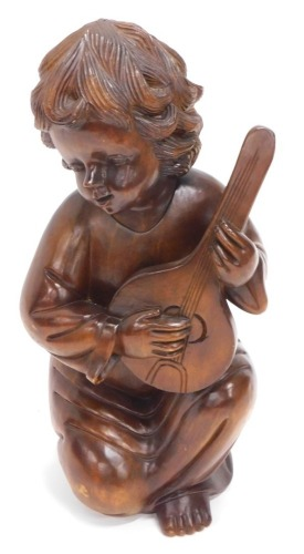 A continental carved hardwood figure, of a young child playing a mandolin, 66cm high.