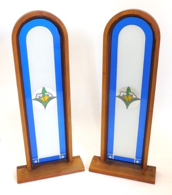 A pair of arched stained glass windows, each mounted in hardwood frames with rectangular bases, 110cm high, 46cm wide.