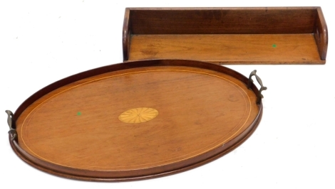 An early 20thC mahogany and boxwood strung oval tray, with brass handles, 52cm wide, and a 19thC portable book rack, 56cm wide.