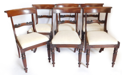 A set of six William IV mahogany dining chairs, each with a shaped bar back and reeded uprights, a drop in seat on turned and fluted legs.
