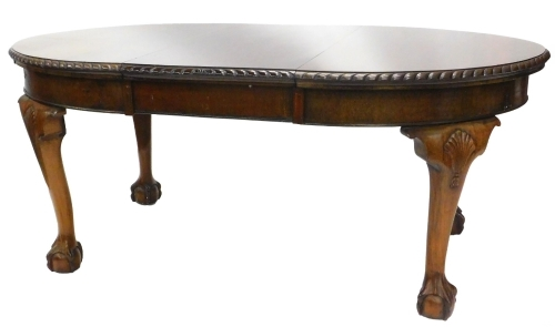 An early 20thC mahogany extending dining table, the oval top with a rope twist carved border, on bulbous and heavy cabriole legs, with ball and claw feet headed by shell carving, 73cm high, the top 105cm x 177cm.