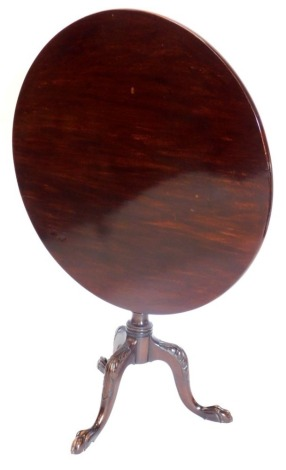 A mahogany tilt top table in George III style, the circular top on a turned part fluted column, on leaf carved cabriole legs with ball and claw feet, 85cm diameter.