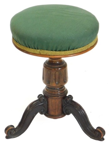 A Victorian rosewood adjustable piano stool, with a green upholstered padded seat, on a turned column and carved tripod base, 47cm high.