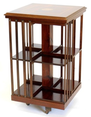 A mahogany revolving bookcase, the square top inlaid with a central patera within a satin wood crossbanded border, above slatted divisions for books, on an egg shaped base, 79cm high, 48cm wide.