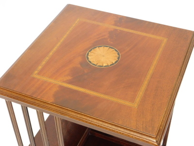 A mahogany revolving bookcase, the square top inlaid with a central patera within a satin wood crossbanded border, above slatted divisions for books, on an egg shaped base, 79cm high, 48cm wide. - 2