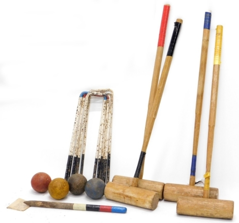 A croquet set, with four mallets, various hoops and four balls.