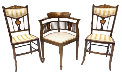 A suite of three chairs, each decorated with marquetry and simulated stringing, comprising a corner chair and two bedroom chairs, of differing upholstery.