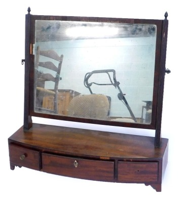 A 19thC mahogany dressing table mirror, with a rectangular plate and reeded supports, on bow fronted base, with three drawers and bracket feet.