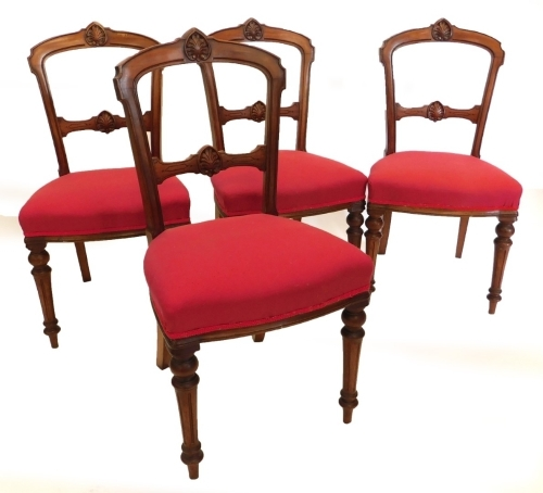 A set of four Victorian walnut balloon back chairs, each with a carved back, a red padded seat on turned fluted legs.