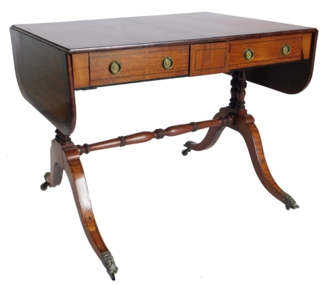 A 19thC satinwood and mahogany sofa table, with ebony stringing, the rectangular top with rounded ends, above two frieze drawers, each with ring handles on twin turned end supports with stretcher, with splayed legs and brass lion mask handles, 71cm high,