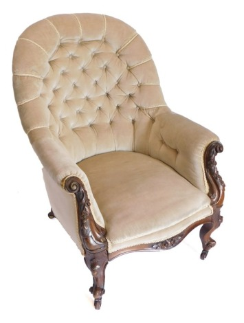 A Victorian walnut armchair, with beige buttoned back, with scroll carved supports on shaped legs with castors.