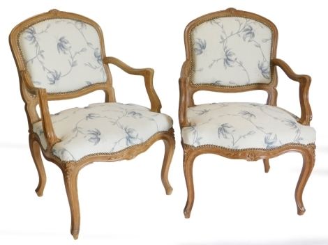 A pair of French style hardwood fauteuil, each with a moulded frame, upholstered in blue and cream floral fabric on cabriole legs. The upholstery in this lot does not comply with the 1988 (Fire & Fire Furnishing) Regulations, unless sold to a known export