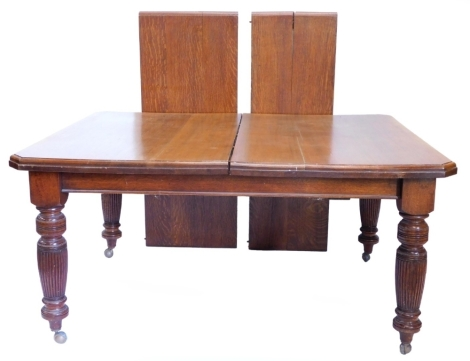 An oak extending dining table, the rectangular top with canted corners, two loose leaves, 73cm high, 118cm deep, 240cm long.