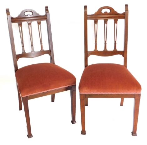 A pair of Edwardian mahogany side chairs, each with a pierced rail back, a padded seat on square tapering legs.