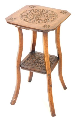 An early 20thC carved hardwood two tier table, on shaped supports, 34cm wide.