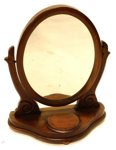 A Victorian mahogany dressing table mirror, the oval plate on shaped supports, a shaped base with a hinged trinket compartment, 49cm wide.