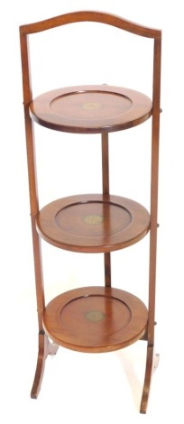 An Edwardian mahogany and boxwood strung three tier cake stand, with transfer printed simulated inlay, 85cm high.
