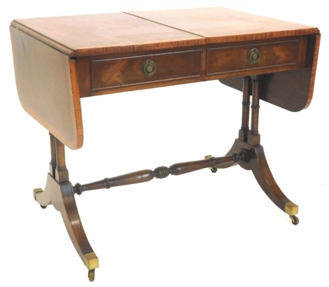 A mahogany and satinwood crossbanded sofa table, the rectangular top with rounded corners above two frieze drawers opposing false drawers, on turned end supports with splayed legs and brass castors, 75cm high, 91cm wide.