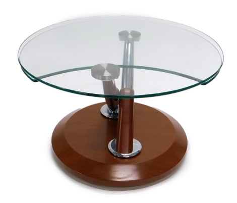 A modern glass topped coffee table, with chrome plated supports and hardwood base, 69cm diameter.