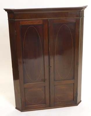 A 19thC mahogany and chequer banded hanging corner cabinet, with a moulded cornice above two doors, each with two panels enclosing shelves, 111cm high, 87cm wide.