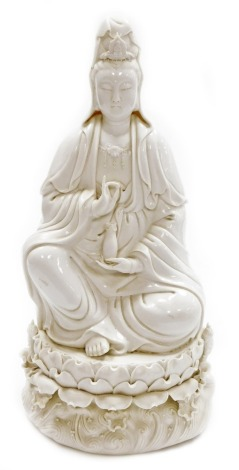 A Chinese blanc de chine figure of Guan Yin seated on a lotus and wave base, impressed mark to the rear, 46cm high. (AF)