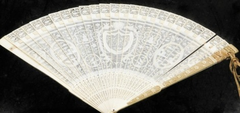 A Canton Chinese ivory pierced fan, with fine detailing, bearing the central shield shaped cartouche with initials AR, with buildings and tree scenes, in display case, 19thC, the case 48.5cm x 34cm the fan 40cm x 25 cm.