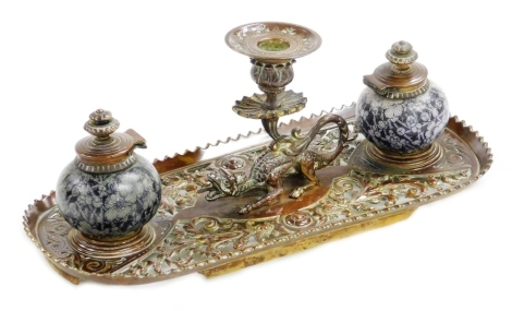 A 19thC continental brass ink stand, with central dragon taperstick and two stoneware inkwells each with textured floral decoration, 32cm wide, 13cm wide, 14cm deep. (AF)