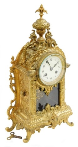 A French cast brass mantel clock, the domed top with a fleur de lis finial and applied with two dragon, with a cream enamel clock face and pendulum in rococo style, 8 day movement, the dial 7.5cm wide, 41cm high overall.