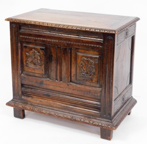 A 19thC continental oak and walnut coffer, with gadroon moulded lift top, scoop carved framing enclosing relief carved profile busts of a male and female, raised on stiles, 67cm high, 72cm wide, 42cm deep.