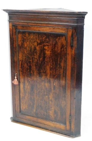 A George III mahogany hanging corner cabinet, with moulded cornice and single door, 105cm high, 79cm wide, 44cm deep.