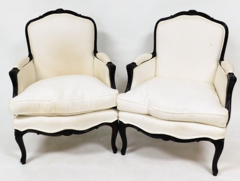 A pair of French style armchairs, with scroll fluted carved arms and cabriole legs, upholstered in a white woven material.