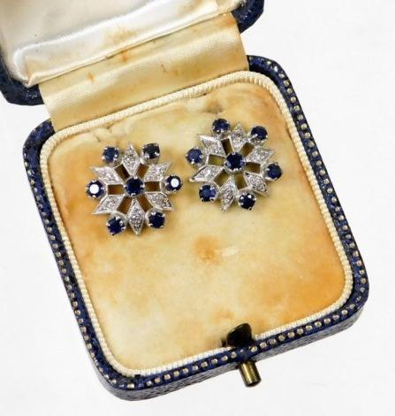 A pair of sapphire and diamond cluster earrings, each with round brilliant cut sapphire in claw setting with illusion set tiny diamonds, in star type detailing, in white metal, unmarked, possibly white gold, in a Oclee & Son of Folkestone fitted case, 4g