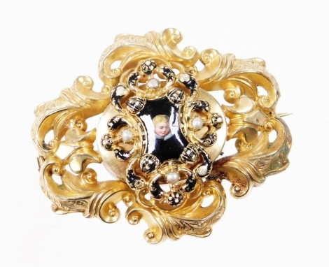 A Victorian memorial brooch, the central panel with enamel detailing, with a figure of child with blonde hair, on a raised border with applied pearl decoration and a bust scroll outer border, with over applied memorial panel back, safety chain and back pi