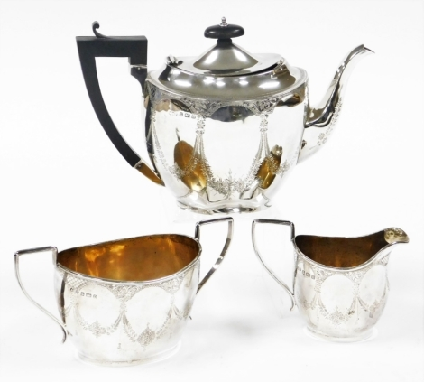 A George V silver Neo Classical design three piece tea service, bright cut decorated with bow drops, flowers and leaves, comprising teapot, milk jug and sugar bowl, Birmingham 1912, 32¾oz gross. (3)