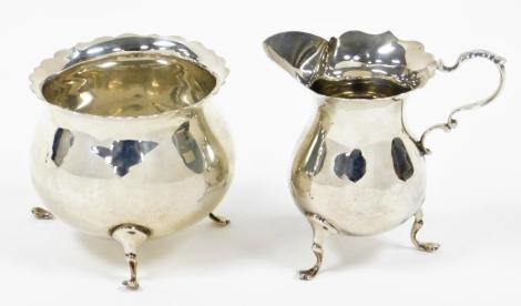 A George V Mappin & Webb silver sugar bowl and milk jug, with wavy rim, each on three feet, London 1926, 4¾oz. (2)