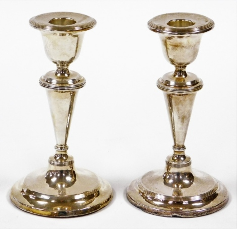 A pair of Edward VII silver dwarf candlesticks, each with a taper stem and stepped base with weighted bases, Birmingham 1906, 15cm high, 23½oz gross.